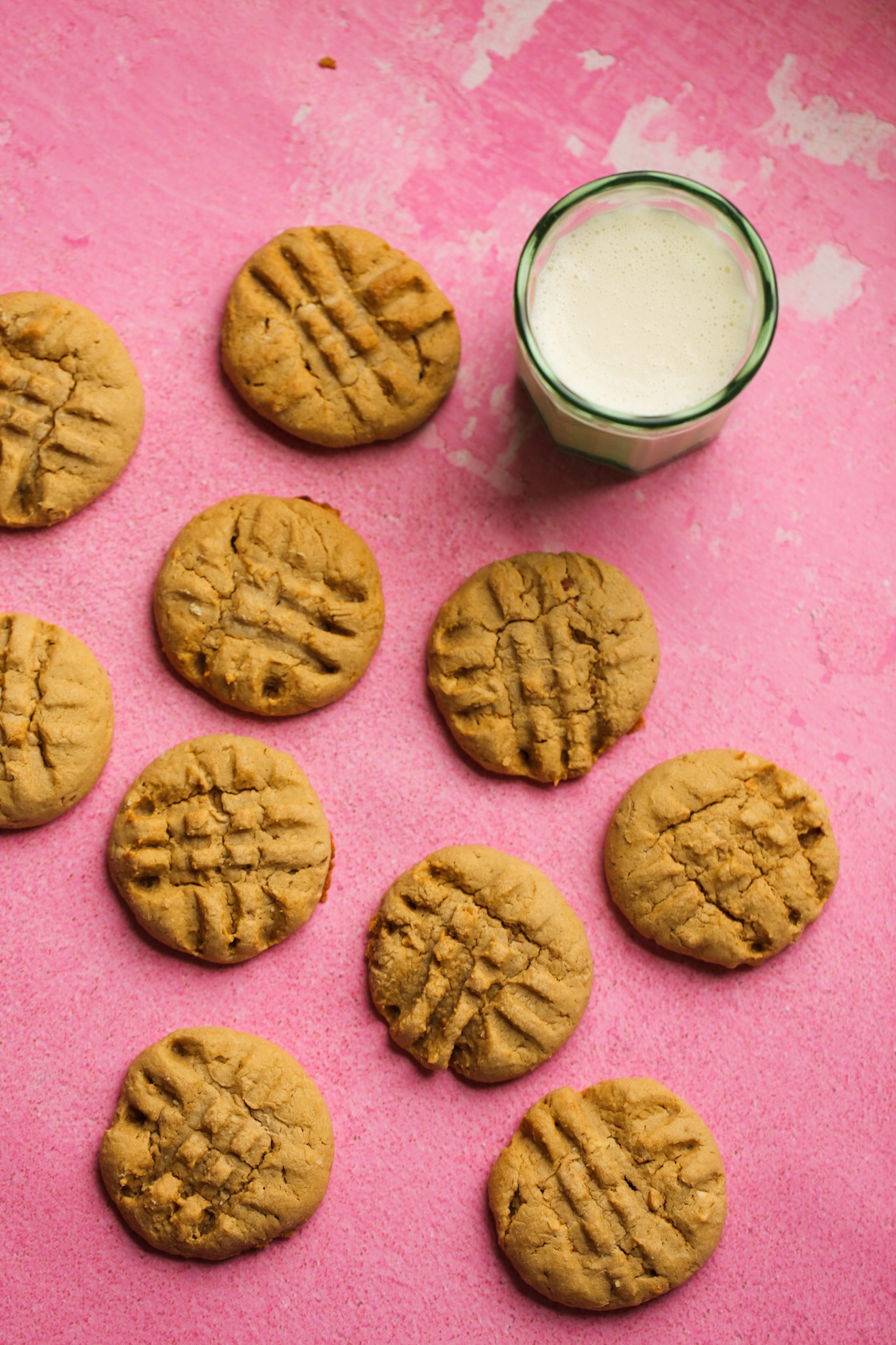 maple peanut butter cookies with a glass of soy milk on a pink surface