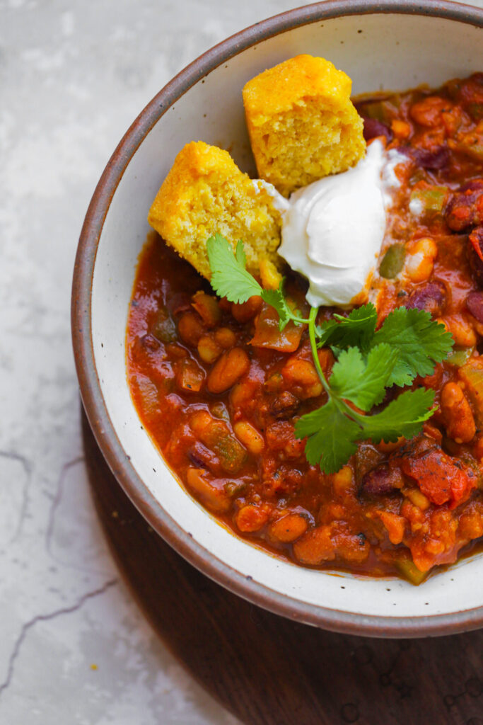 veggie chili with cornbread and sour cream in a bowl