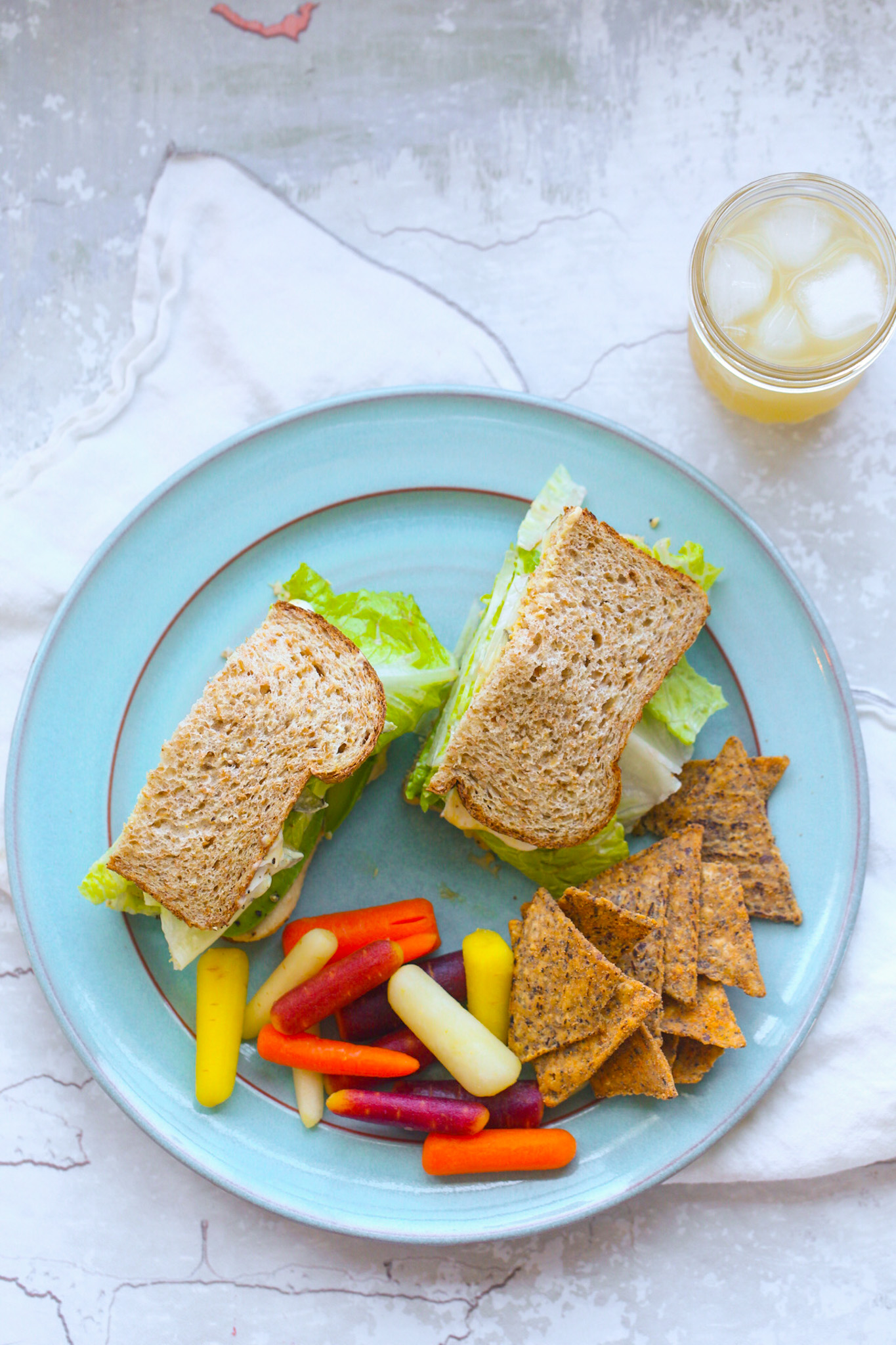 lunch plate with avocado hummus sandwich and carrots