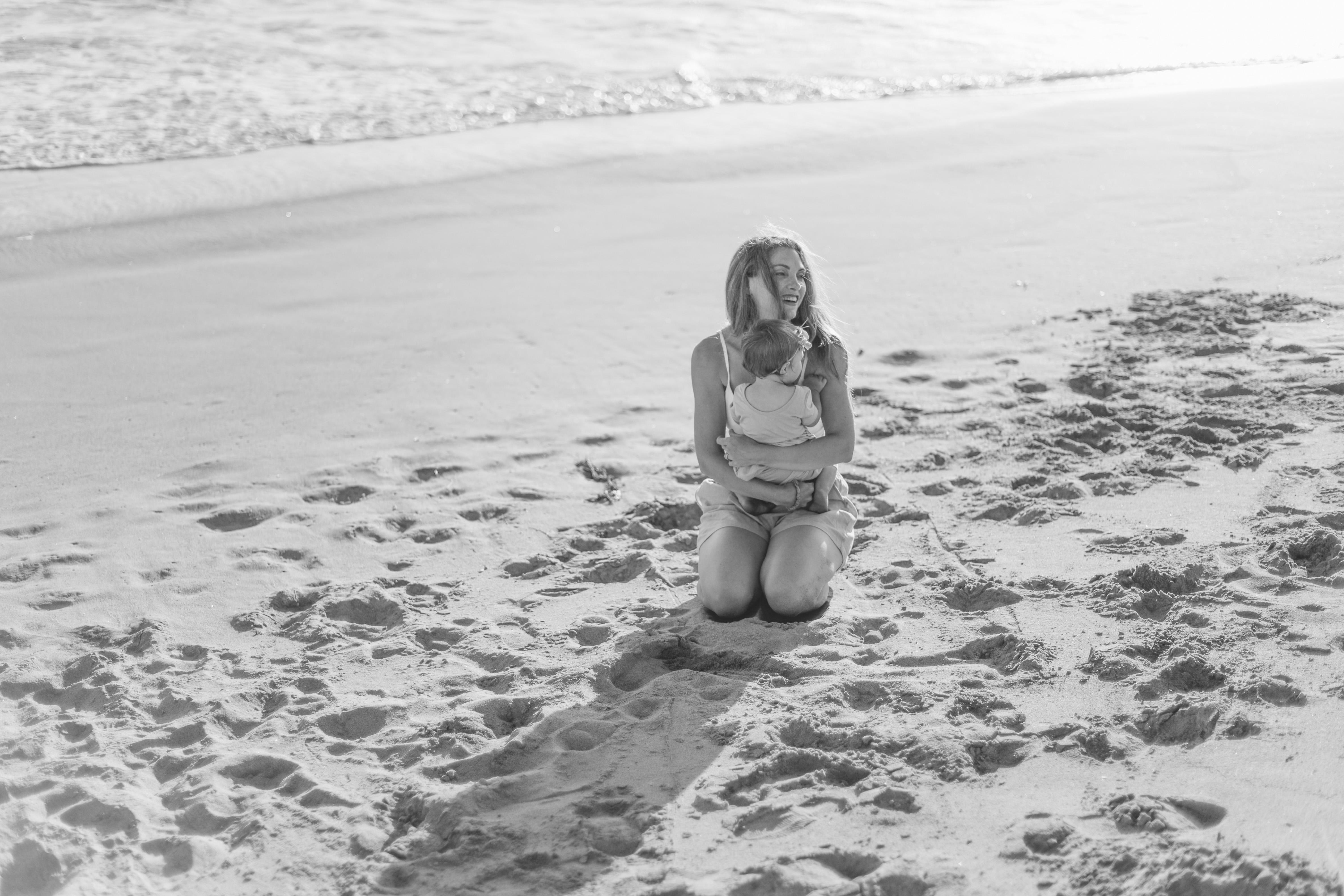 mommy hugging baby beach California
