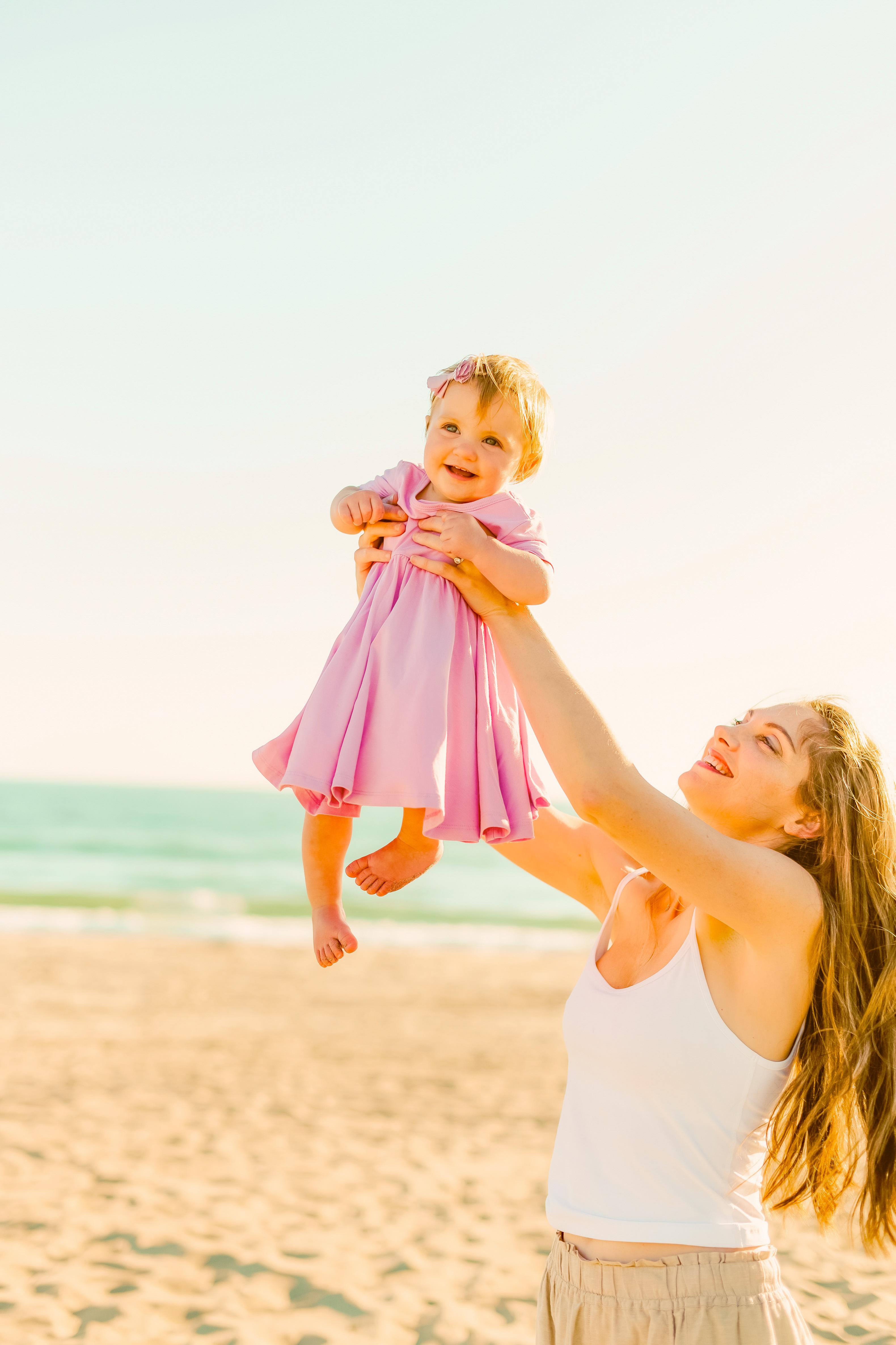 Rosalie in a pink dress baby beach